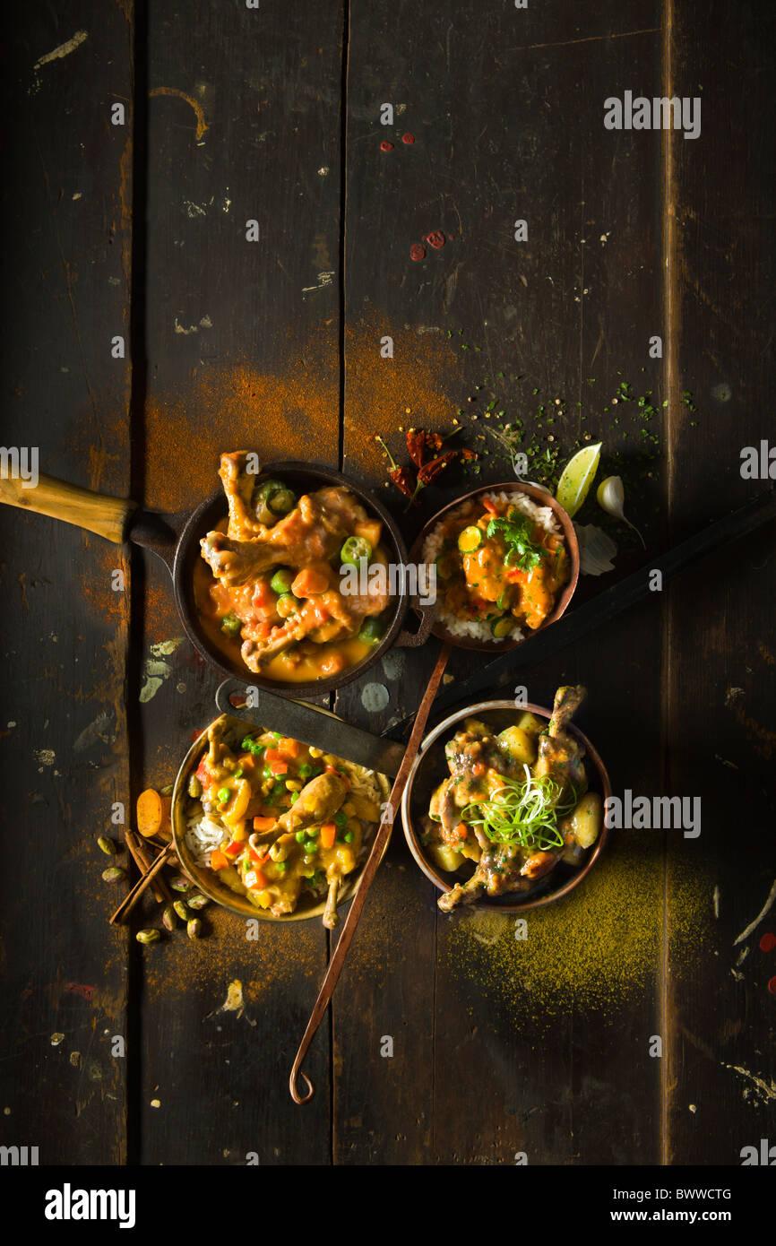 Vier ethnischen Huhn Eintöpfe in vier verschiedenen rustikalen Gefässen auf einem rustikalen Holztisch. Stockbild