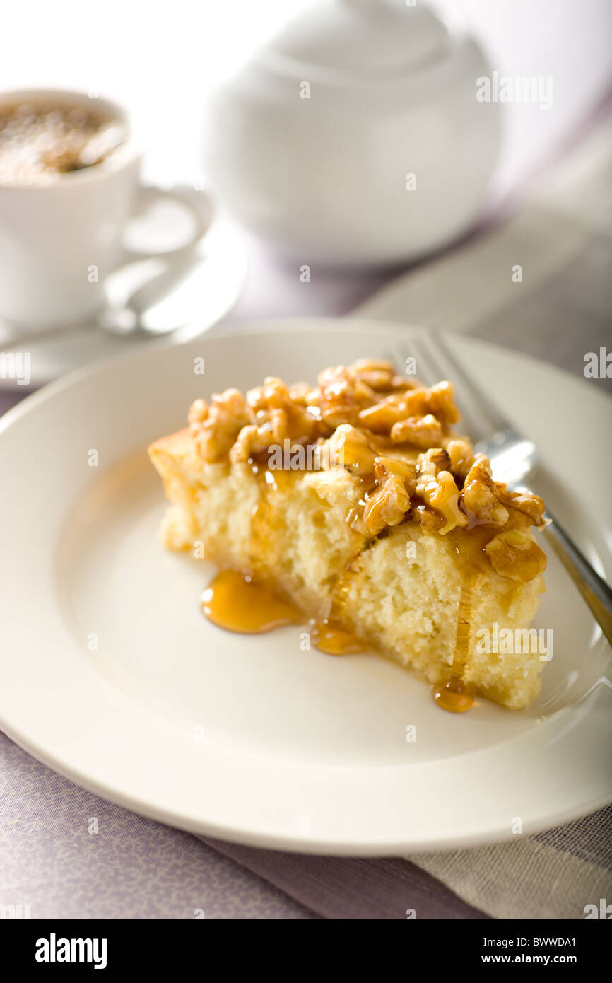 Ahorn-Rum-Pudding-Kuchen garniert mit gehackten Walnüssen und Ahornsirup. Stockbild