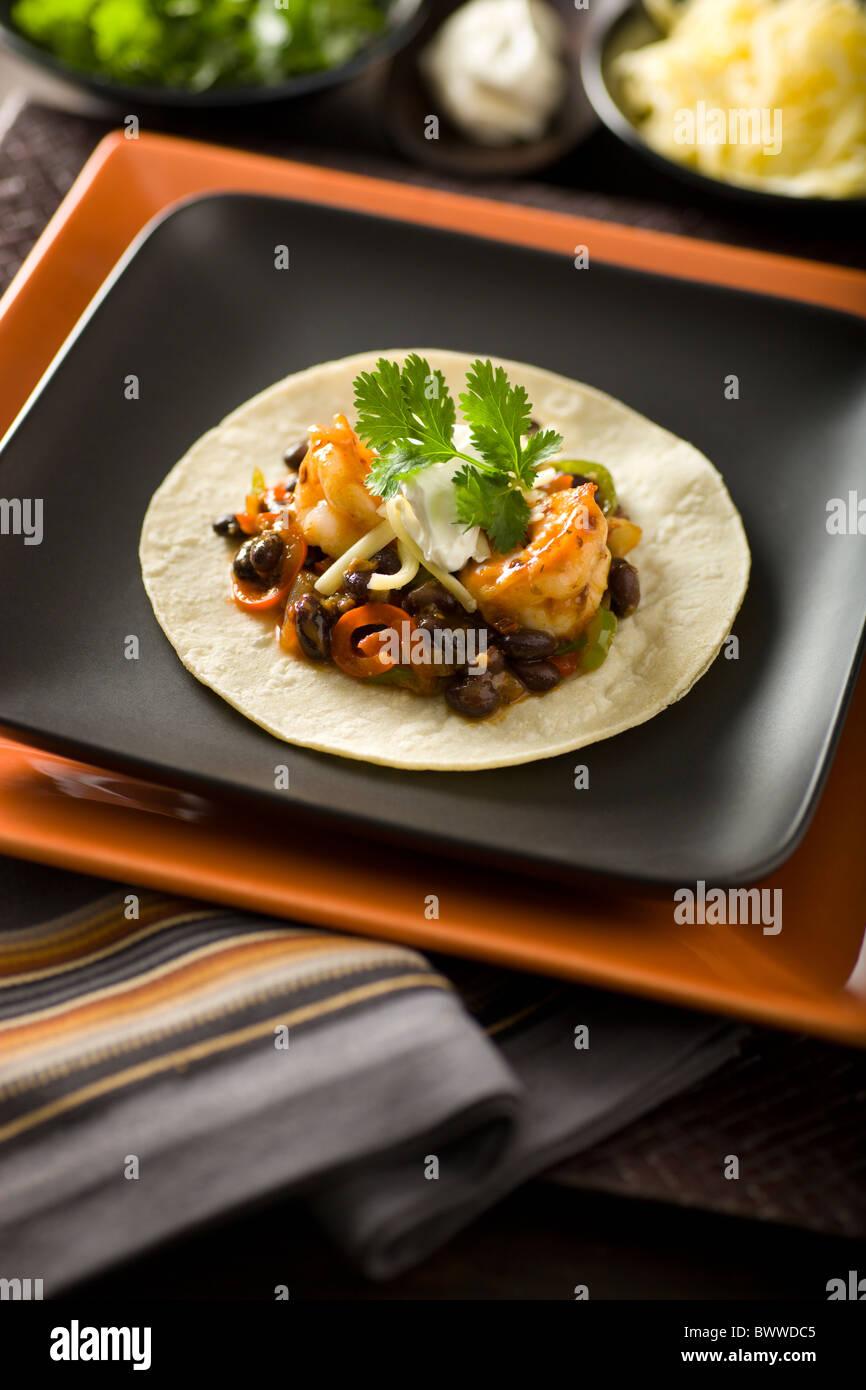 Mexikanische Chipotle Garnelen anbraten mit roter und grüner Paprika-Streifen, schwarze Bohnen, Monterey Jack, Stockbild