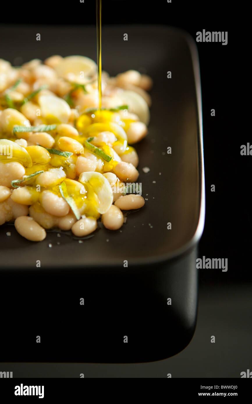 Gekochte weiße Bohnen serviert mit Knoblauch, Salbei und Extra Natives Olivenöl Stockbild