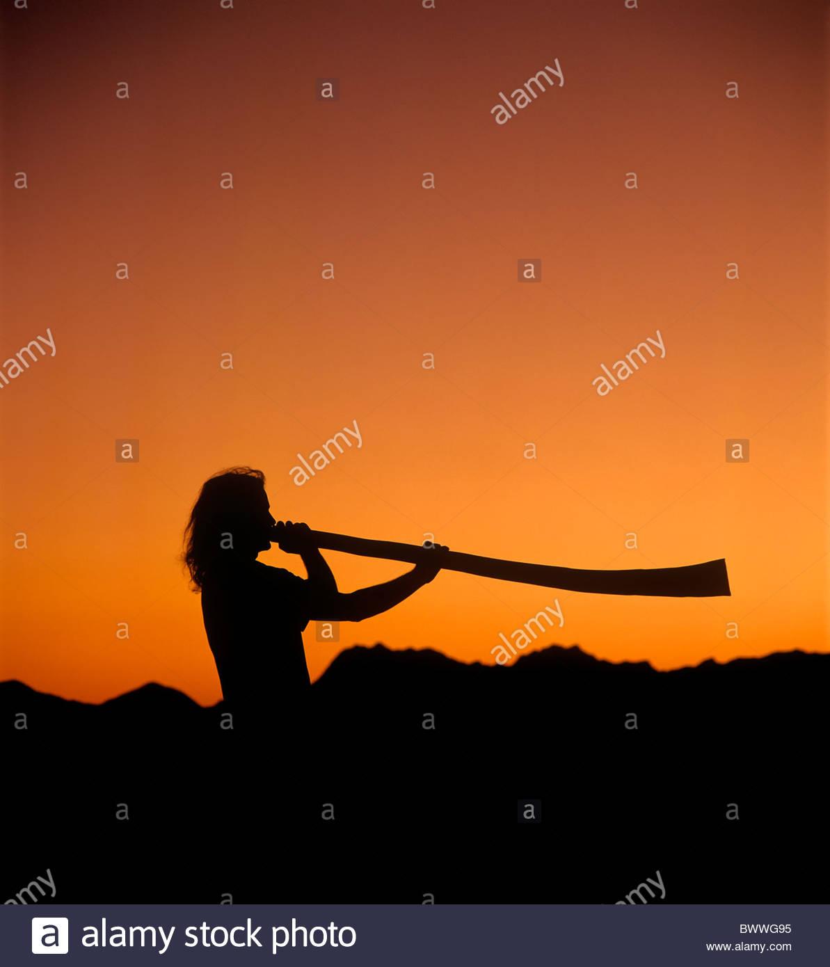 Man spielt ein Didgeridoo bei Sonnenuntergang mit Tucson Berge im Hintergrund Silhouette Orange und schwarz Stockfoto