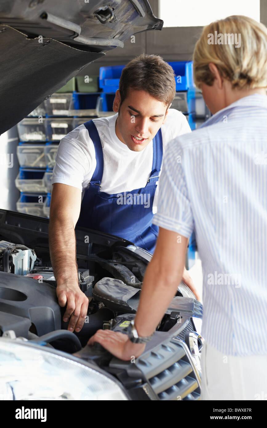 Mechaniker mit weiblichen Kunden in Autowerkstatt zu reden. Stockbild