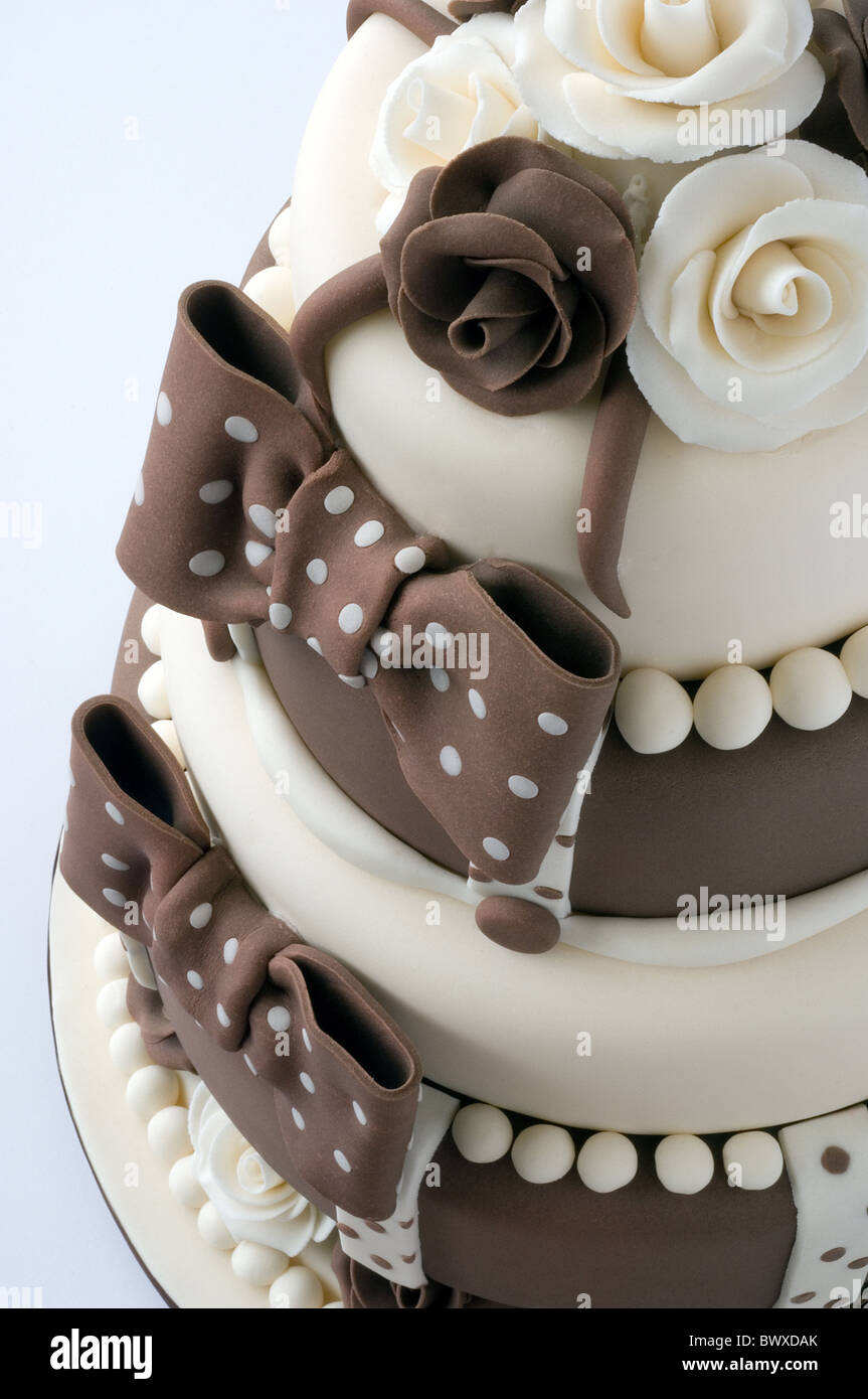 Ein braun und Creme iced Feier Kuchen mit Rosen und Schleifen Stockfoto