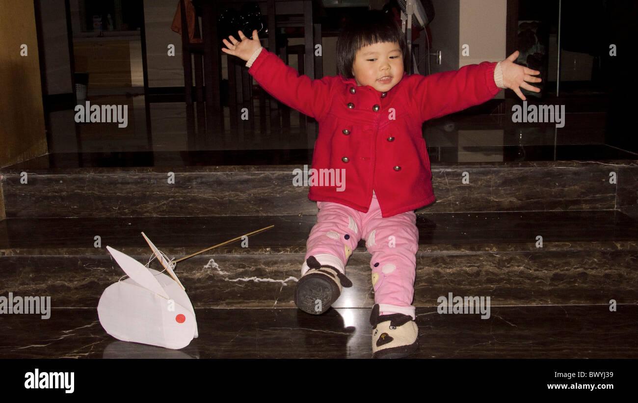 Chinesisches Mädchen spielen mit einer traditionellen Kaninchen Laterne während Festival Tempel Frühjahrsmesse, Stockbild