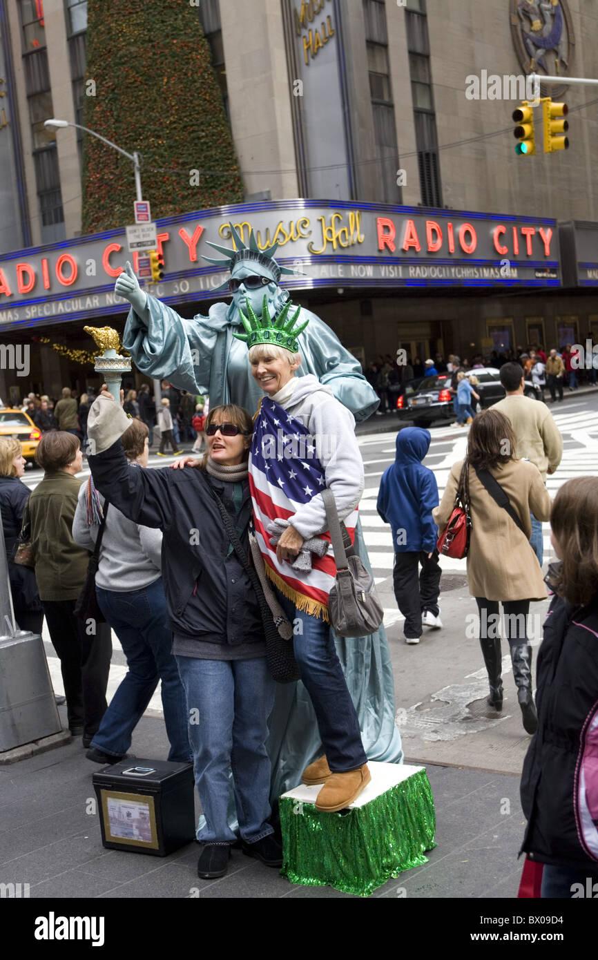 Performance-Künstler wie die Statue of Liberty interagiert mit Touristen, etwas Geld in der Urlaubszeit von Stockbild