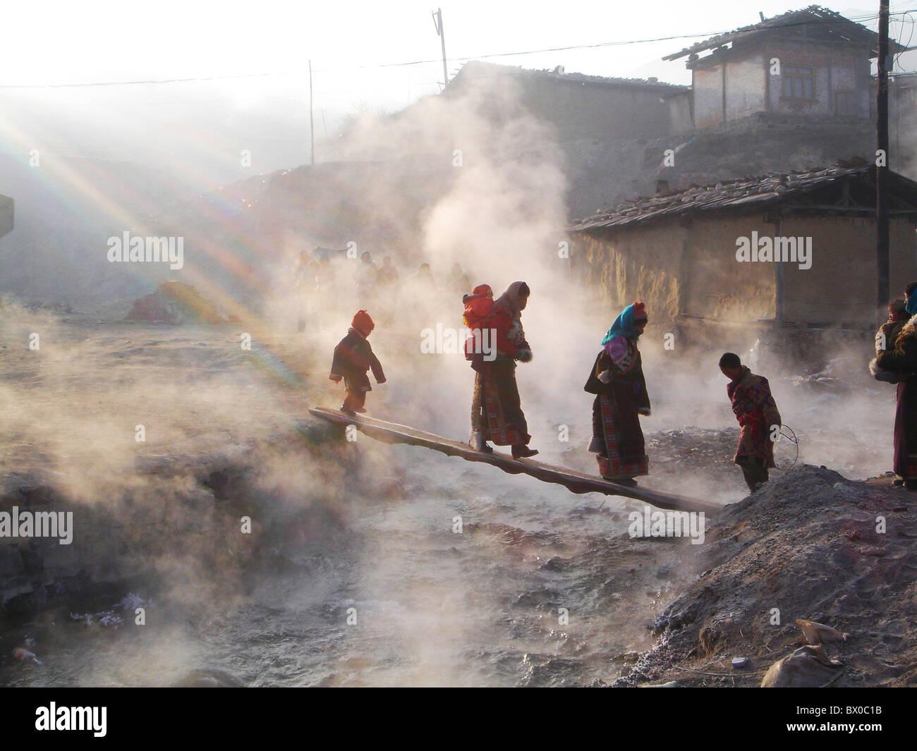 Tibeter, die Kreuzung der Sprudel durch ein schmales Holzbrett, Langmu Kloster Gannan, Gansu, China Stockbild
