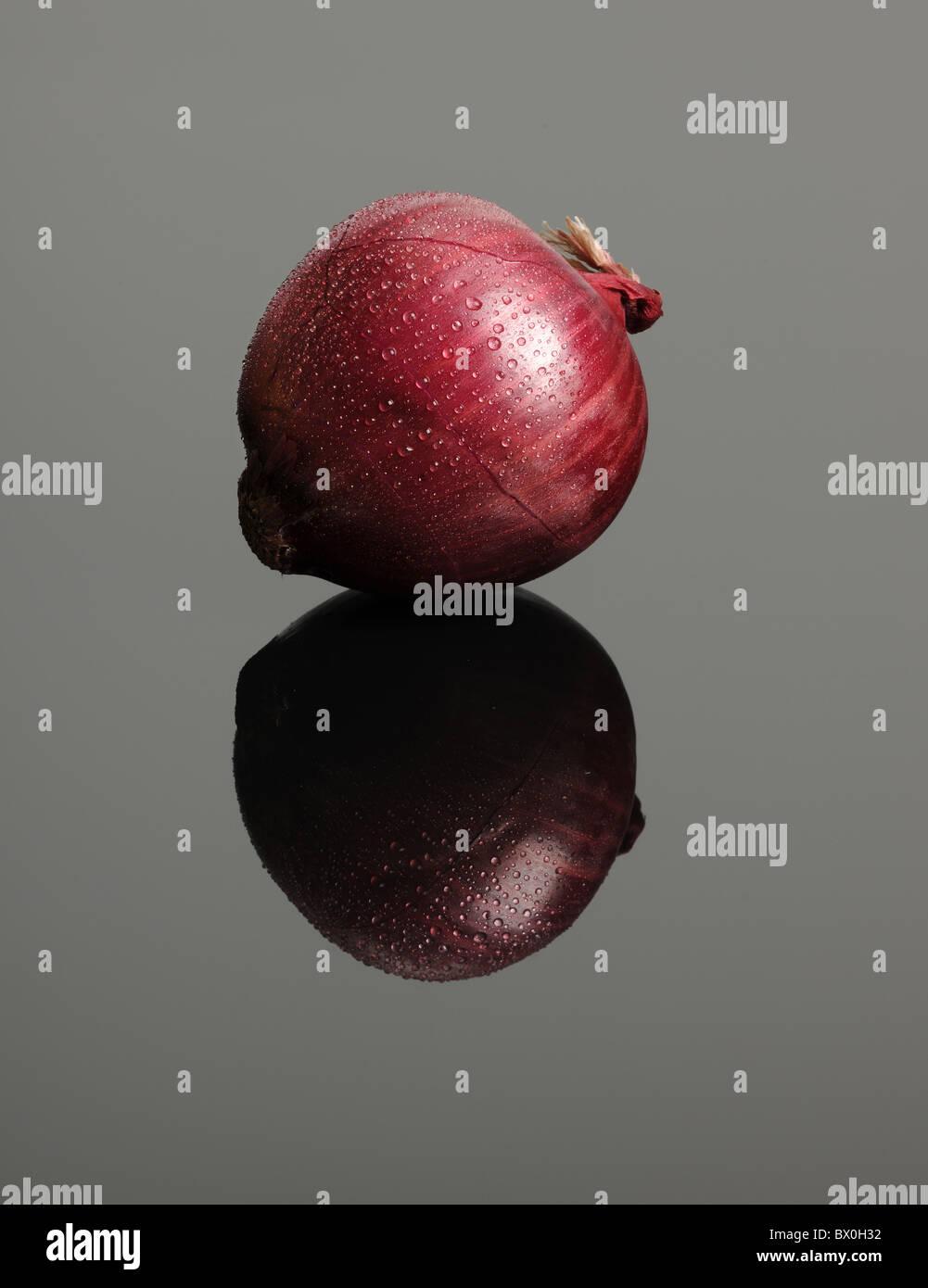 Rote Zwiebel mit Kondensation Tröpfchen auf Glastisch Stockbild
