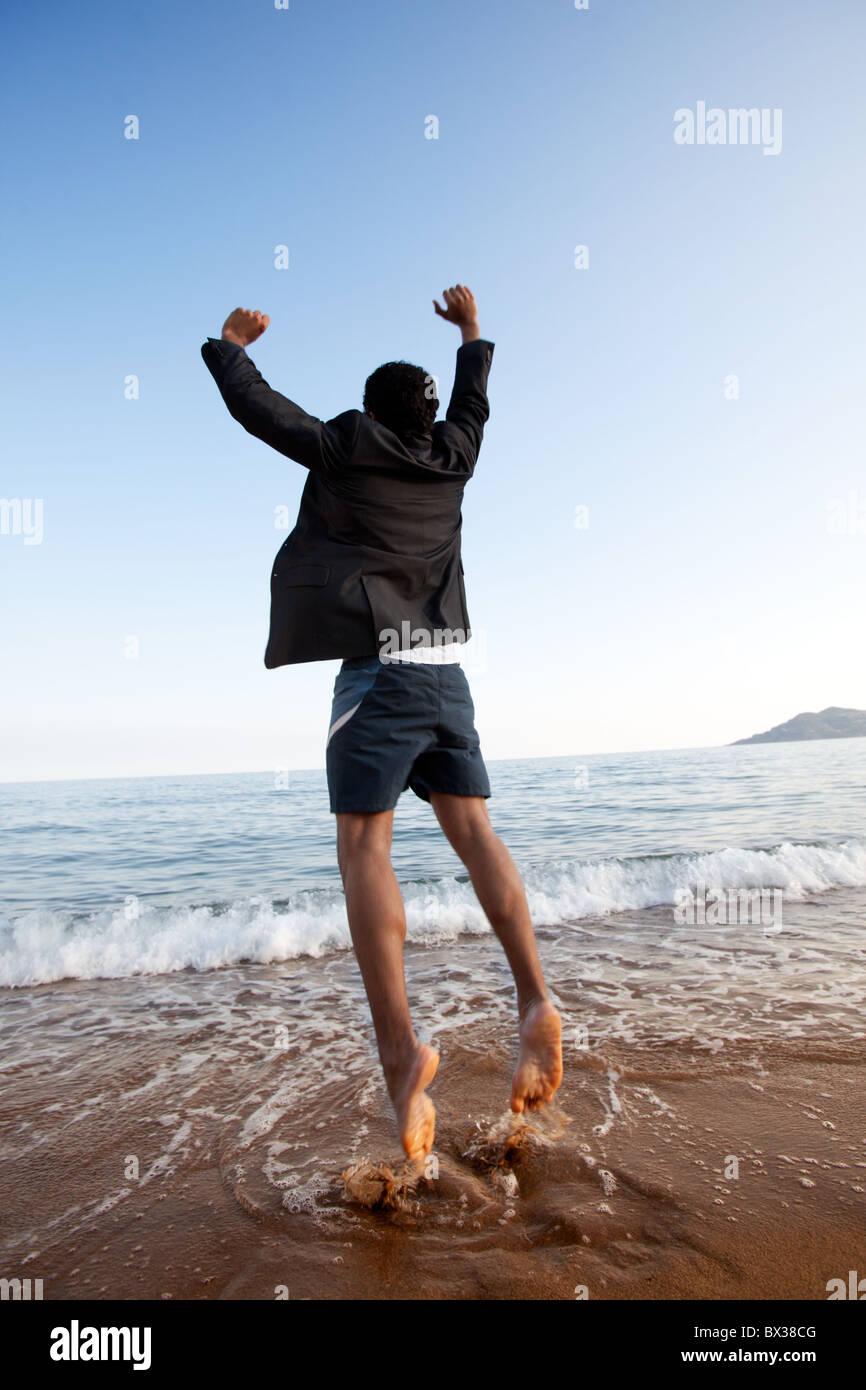 Ein Business-Mann springt auf den Strand, die Freiheit, das Erfolgskonzept Stockbild