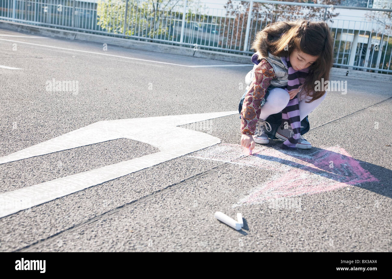 junges Mädchen zeichnen Pfeil in Gegenrichtung von Verkehrszeichen Stockbild