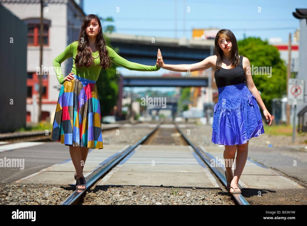Mädchen im Teenageralter balancieren auf den Bahngleisen Innenstadt; Portland, Oregon, Vereinigte Staaten von Amerika Stockfoto