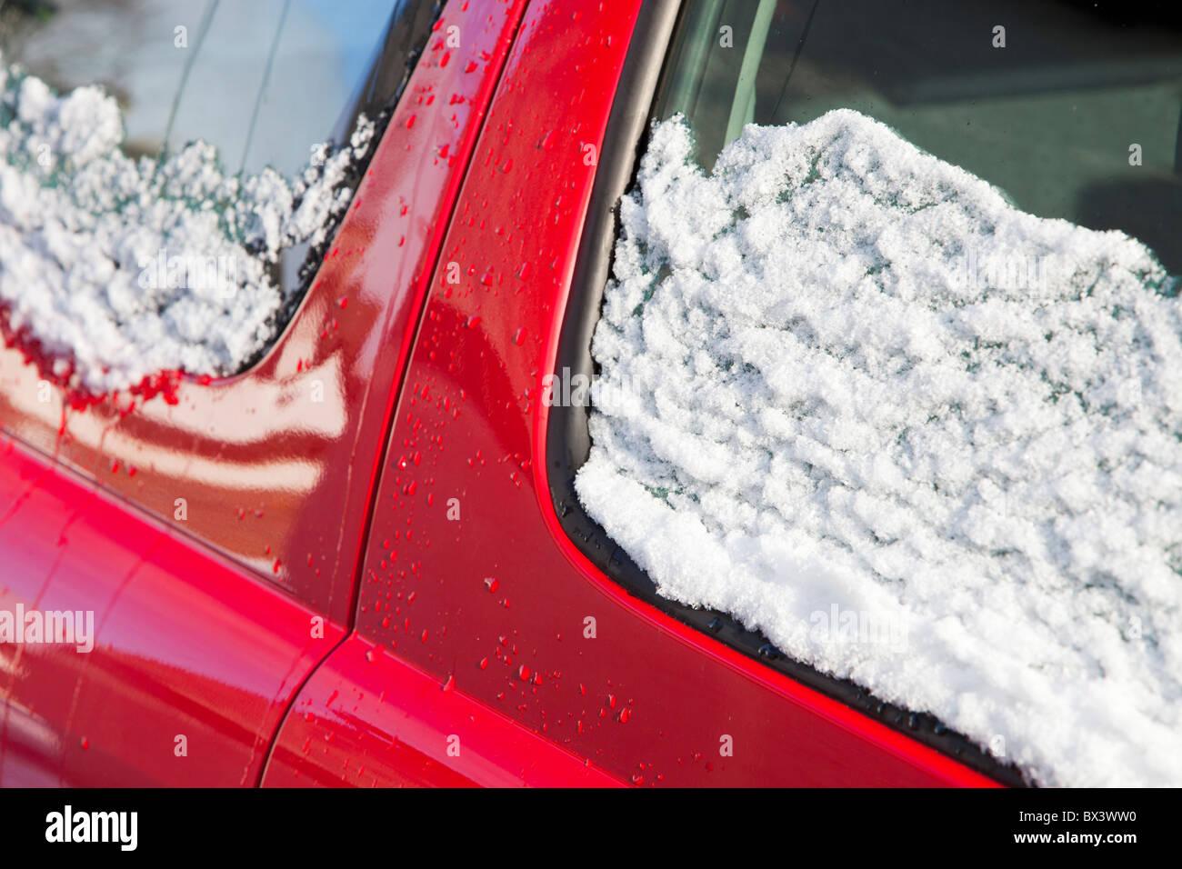 Schmelzender Schnee auf ein Auto. Stockbild