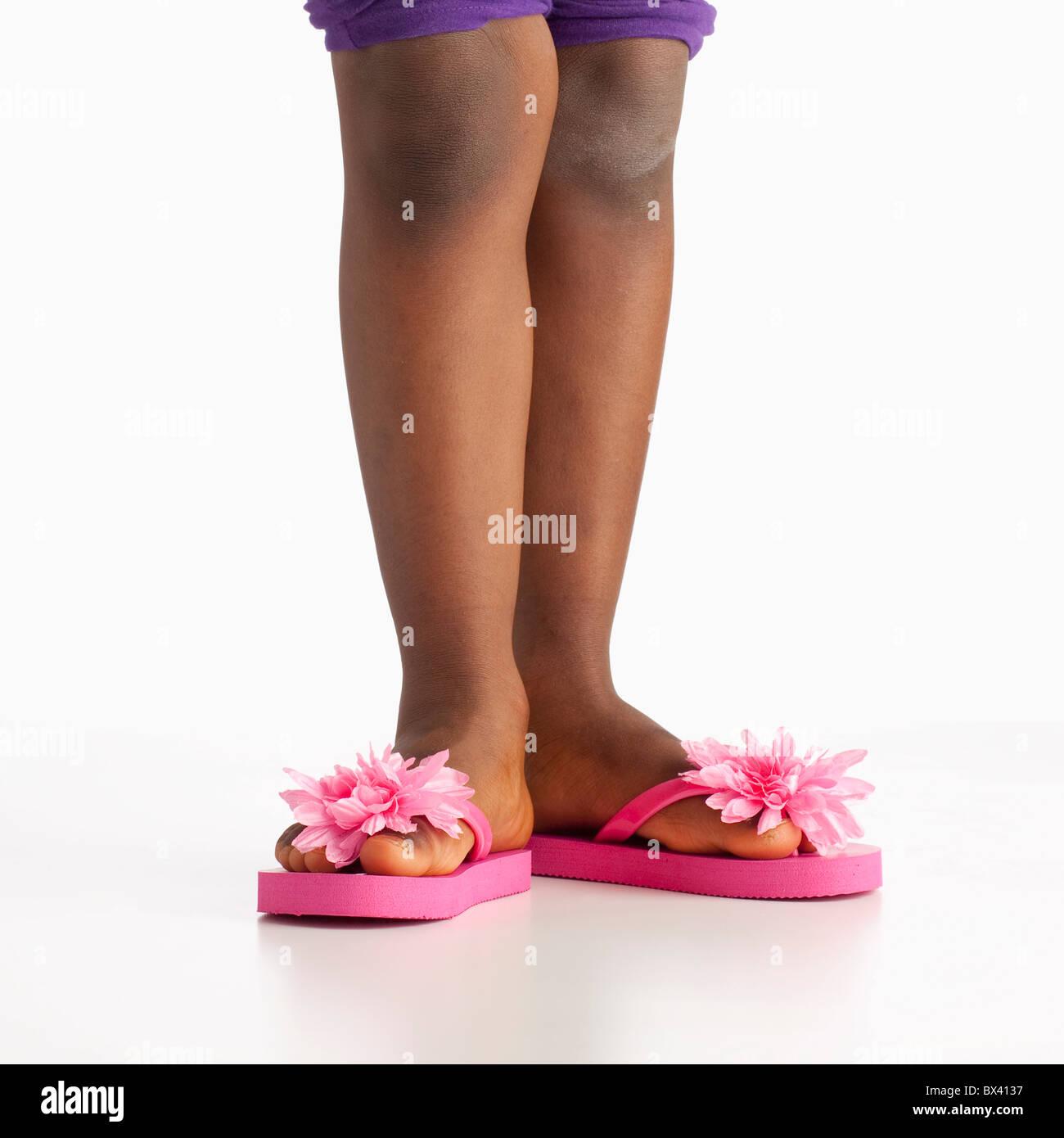 Eine Mädchen trägt Flip Flops mit rosa Blüten Stockfoto
