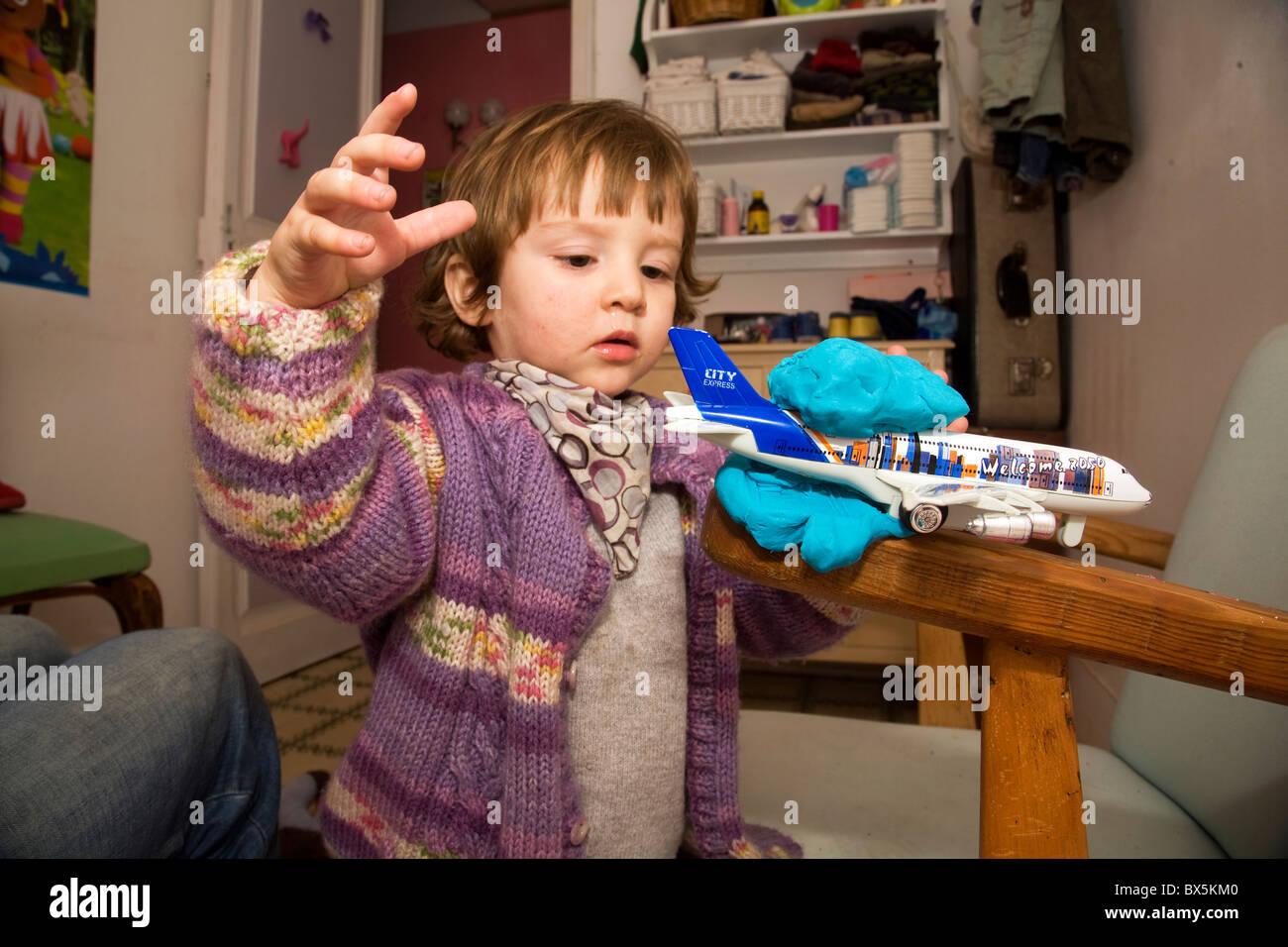 22 Monate junge spielt mit seinem Spielzeugflugzeug in seinem Schlafzimmer Stockbild