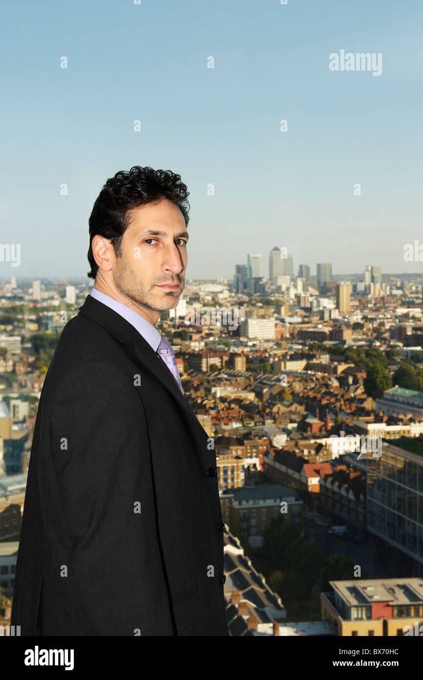 Porträt von Executive mit Blick auf Stadtlandschaft hinter ihm Stockbild