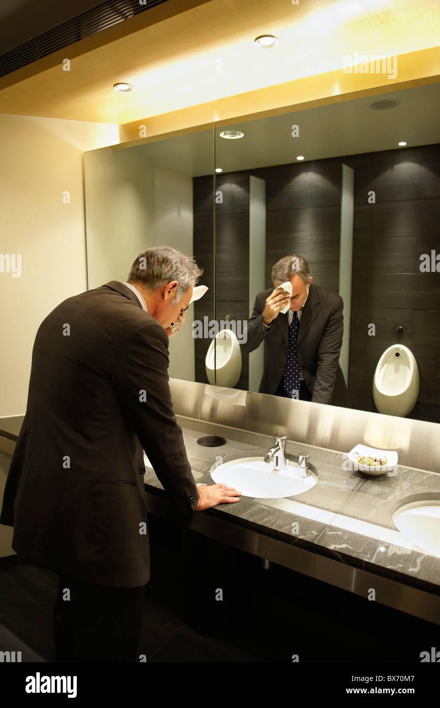 Ängstlich Geschäftsmann vor Spiegel in der Toilette/öffentliche Toilette Stockbild