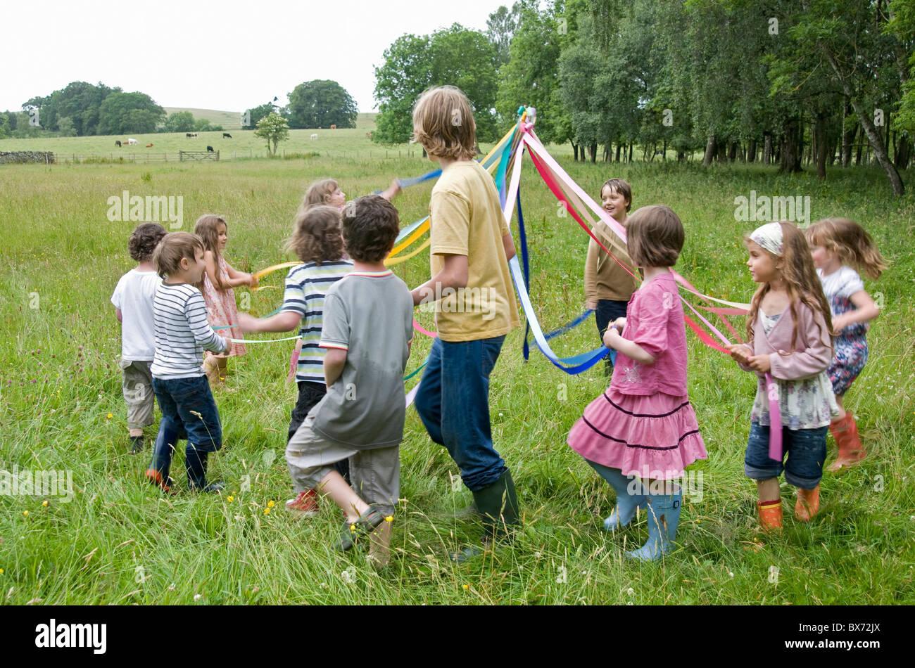 Kinder tanzen um den Maibaum in Wiese Stockbild