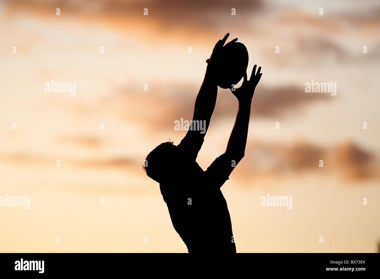 Rugby-Silhouette-Spieler mit Ball mit Sonnenuntergang Stockfoto
