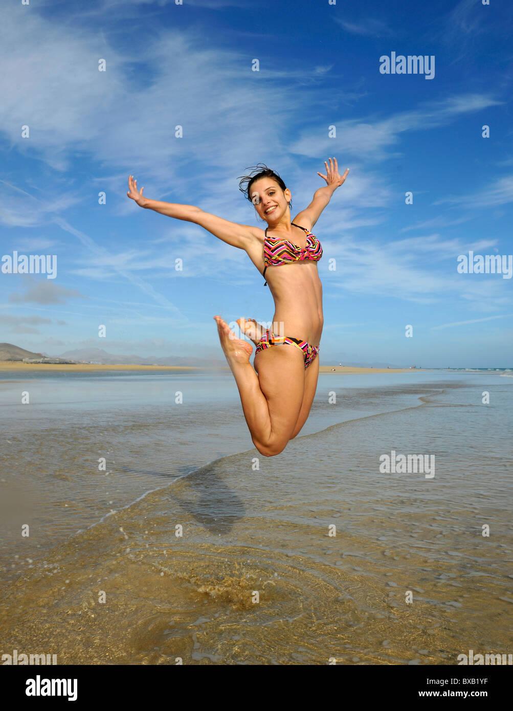 Springen Sie in die Luft, junge Frau am Meer, symbolisches Bild für Vitalität, Lebensfreude, Strand Playa Stockbild