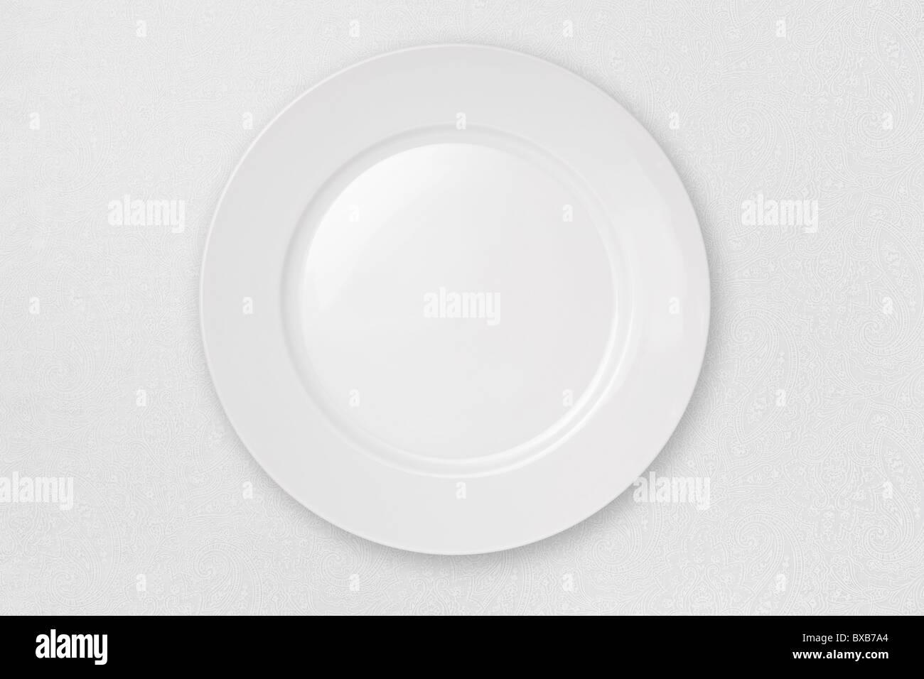 Leeren Teller isoliert auf einem weißen Tischtuch. Stockbild