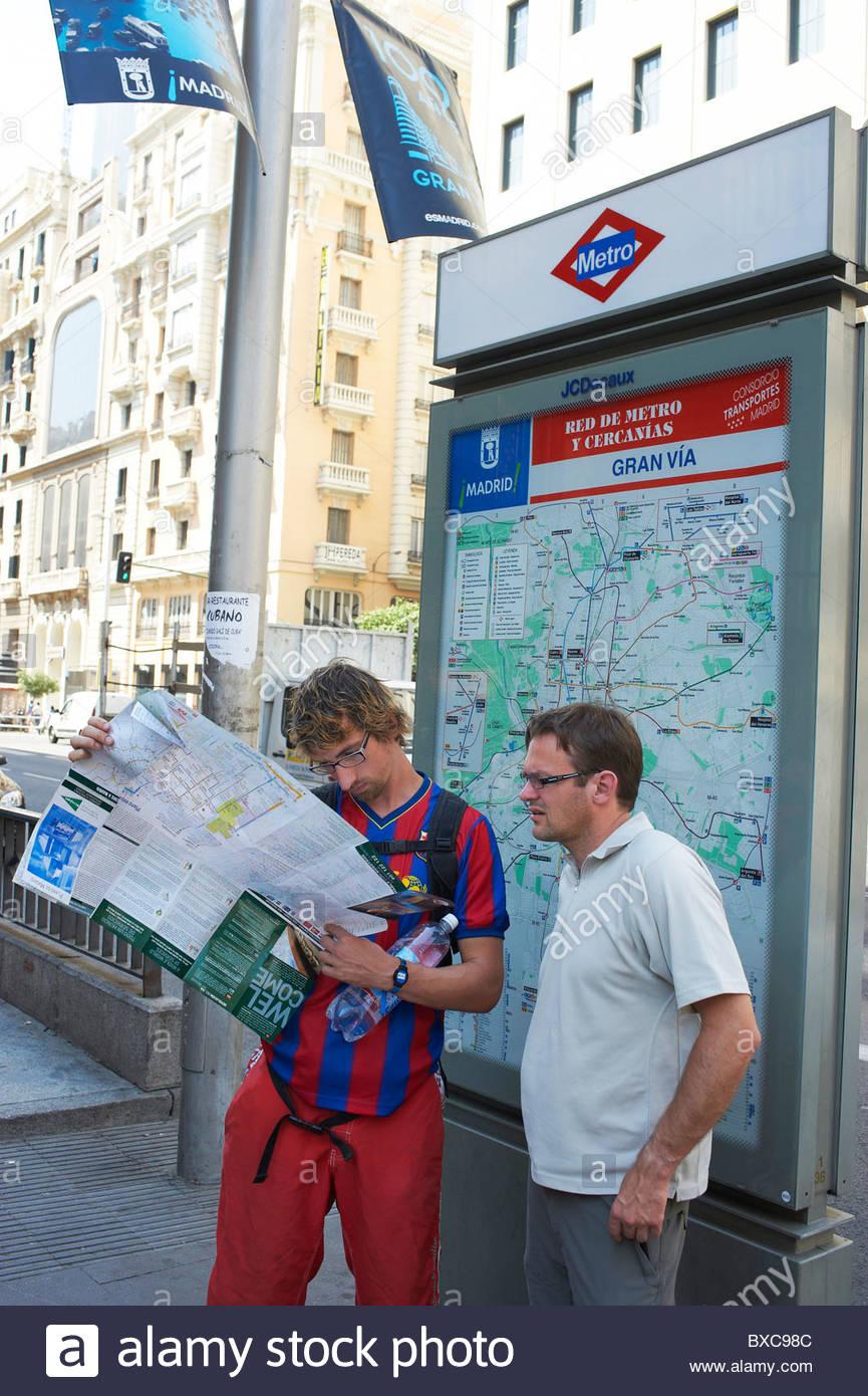 Touristen auf der Straße mit Blick auf einen Reiseführer Karte in Madrid Gran Via Bereich verloren Stockbild