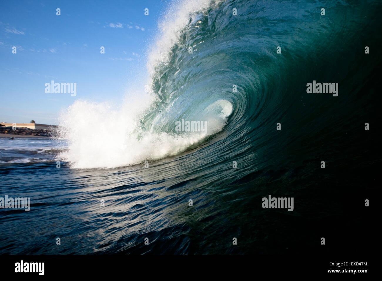 Eine große Welle bricht in Küstennähe. Stockbild