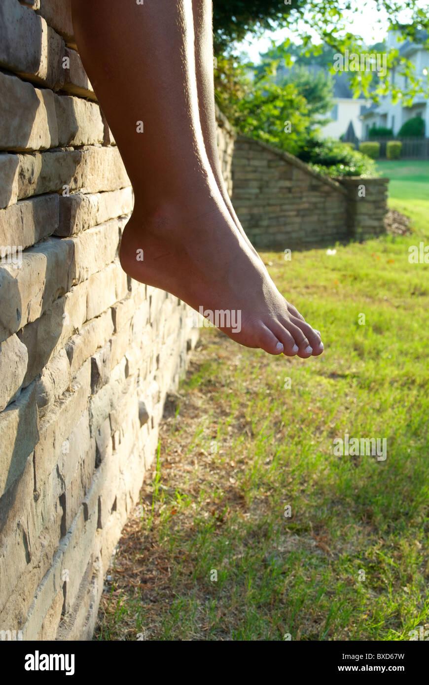 Kleiner junge Beine hängen von einer Steinmauer umgeben. Stockbild