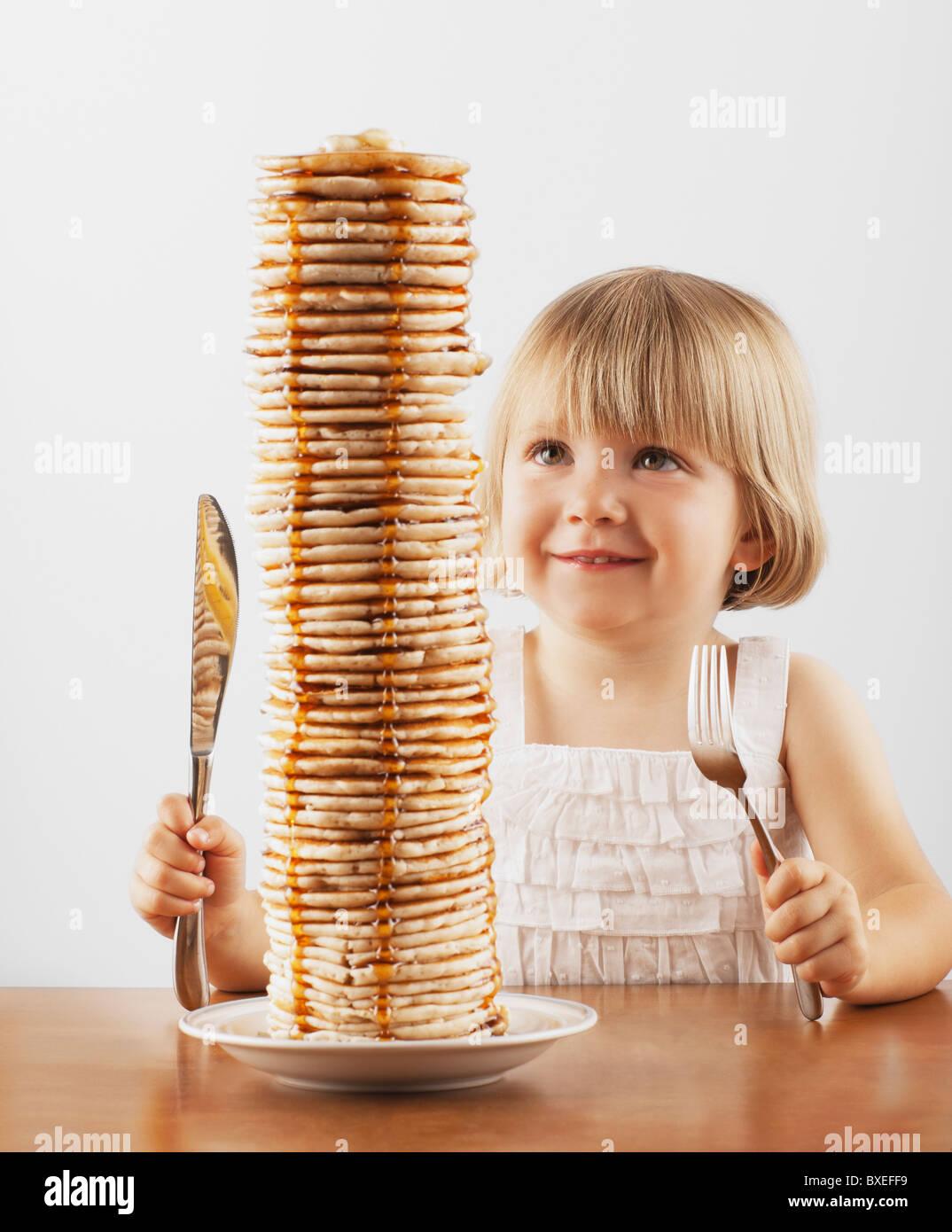 Junges Mädchen sitzt hinter einem hohen Stapel von Pfannkuchen Stockbild