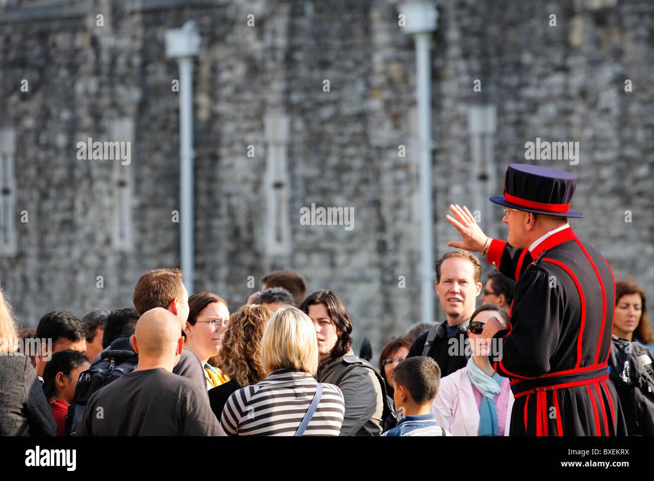 Beefeater mit einer Reisegruppe im Tower of London, UK Stockbild