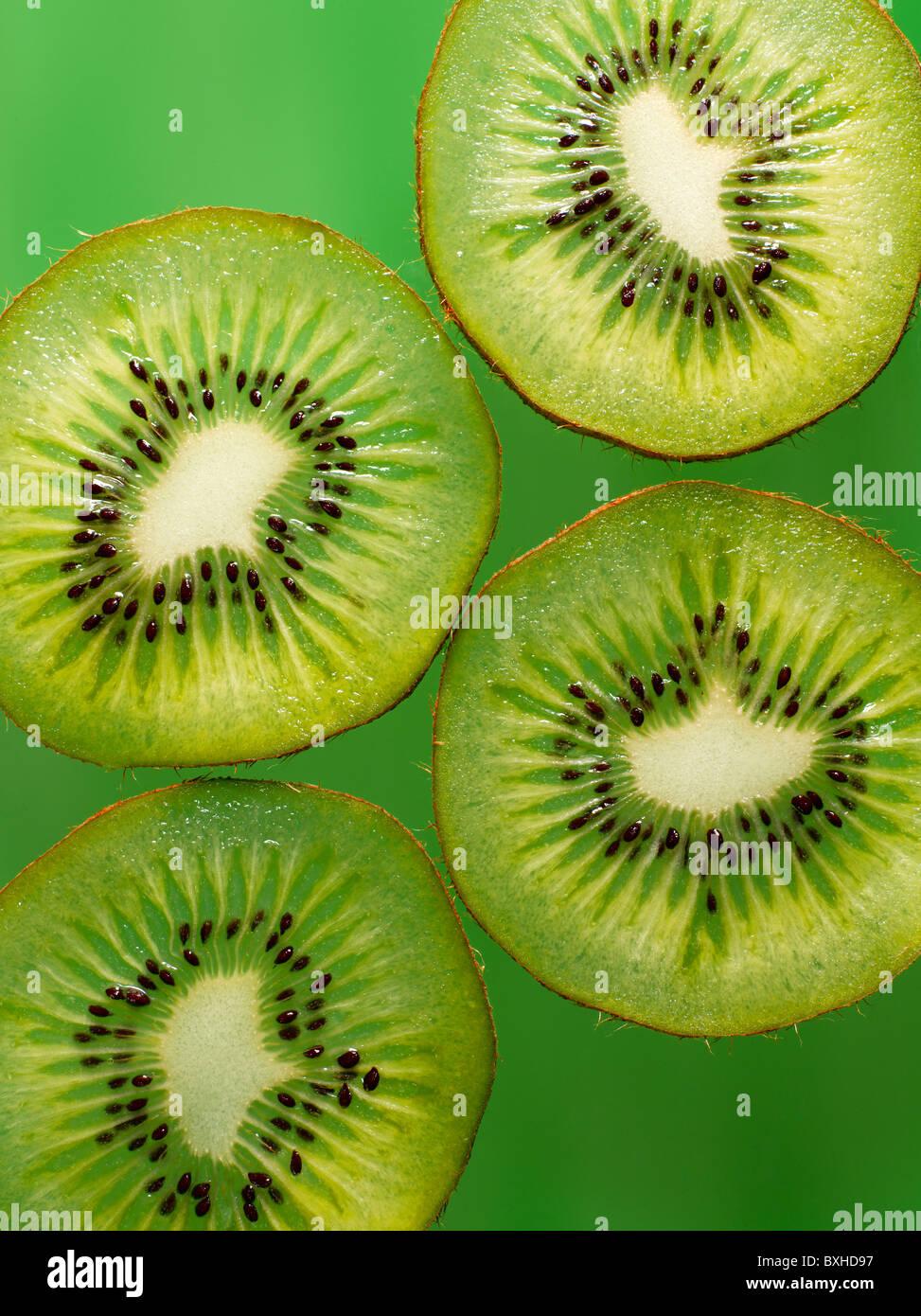 Kiwi FRUCHTSCHEIBEN auf grünem Hintergrund Stockbild