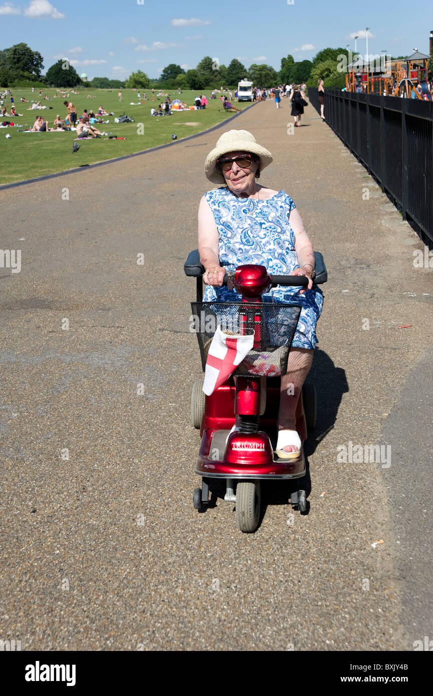 Ältere Frau auf Mobilität Roller, London, England, UK Stockbild