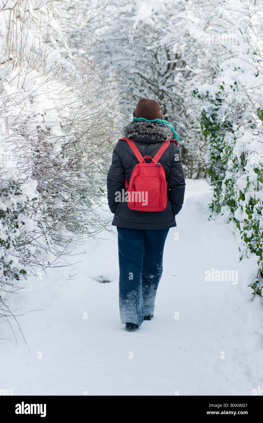 Frau zu Fuß entlang einer Schnee bedeckten Strecke in Redditch, Worcestershire. Stockfoto