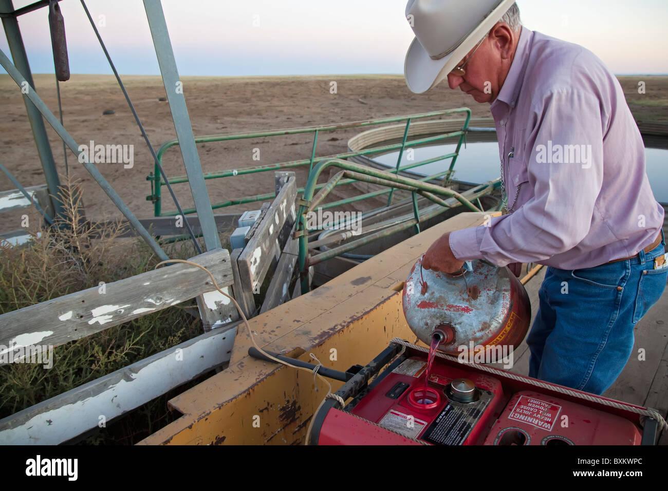 Rancher füllt Generator mit Dieselkraftstoff, Wasserpumpe für Rinder Stockbild