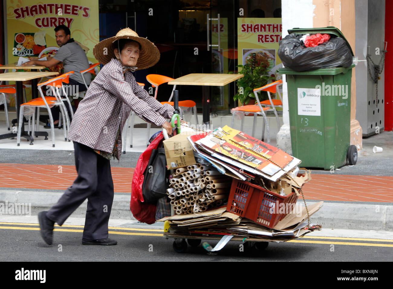 Singapur: arme Frau sammeln Papier und Kartons, Schieben Karren auf Straße Stockbild