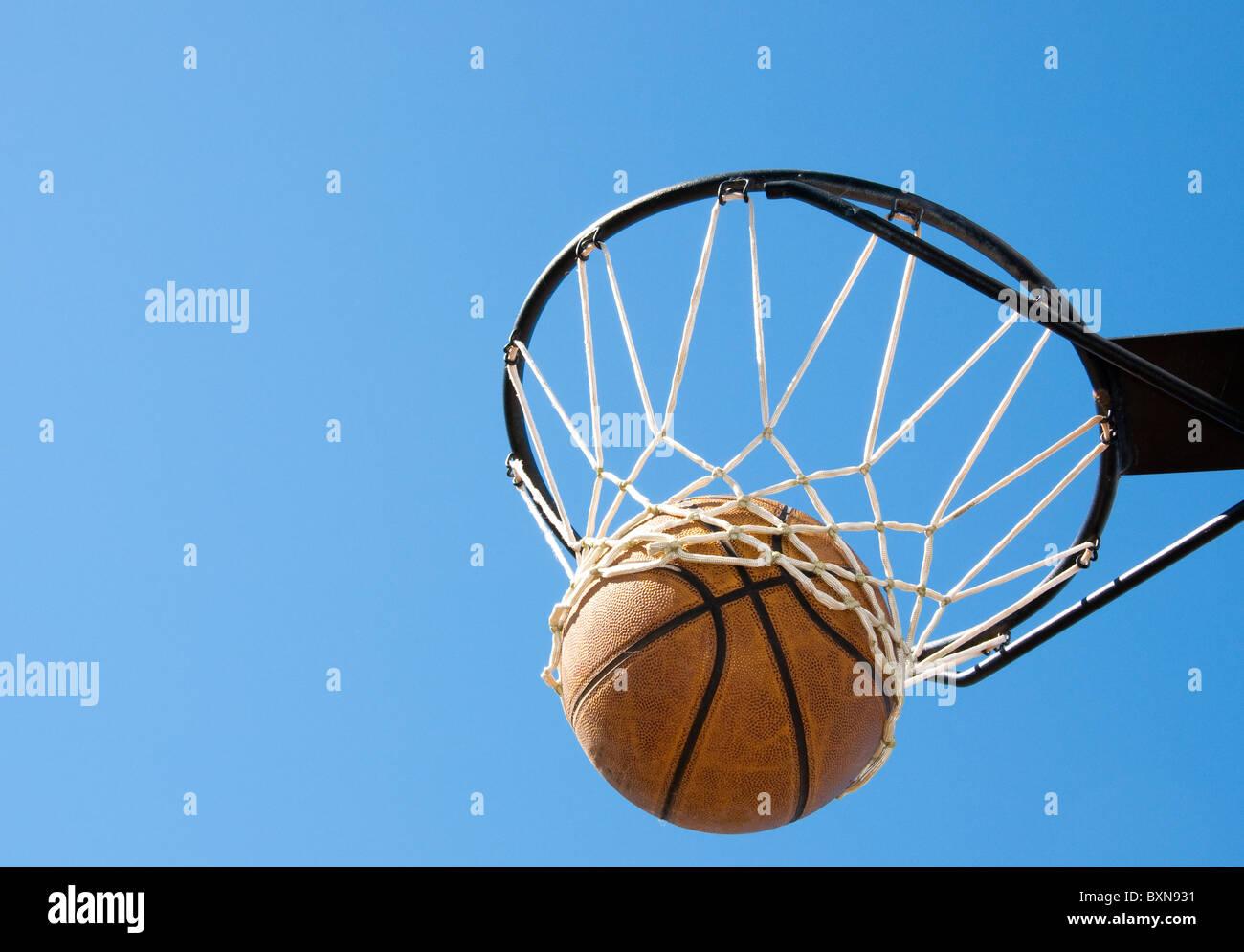 Basketball im Netz - abstraktes Konzept für den Erfolg, seine Ziele zu erreichen Stockbild