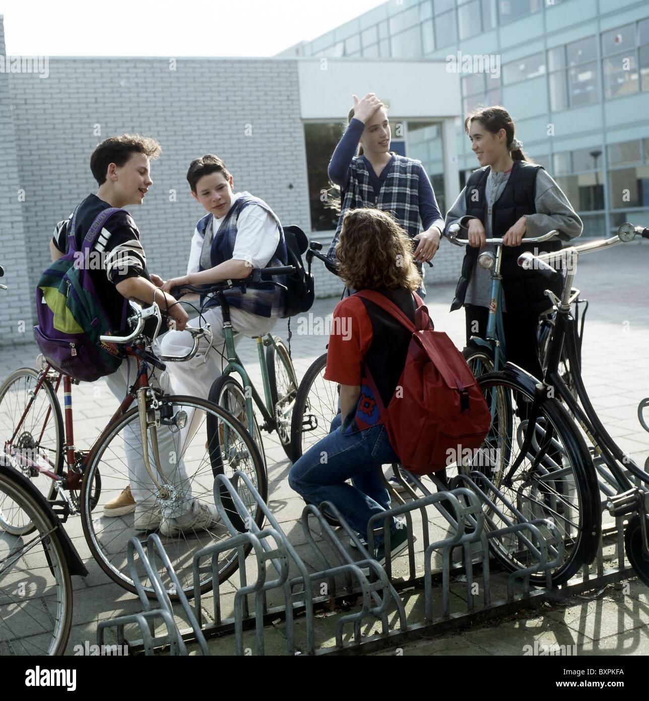 80er - 90er Jahre Jugend: Jugendliche auf Schulhof chatten außerhalb in der Nähe Fahrradverleih parkplatz Stockbild