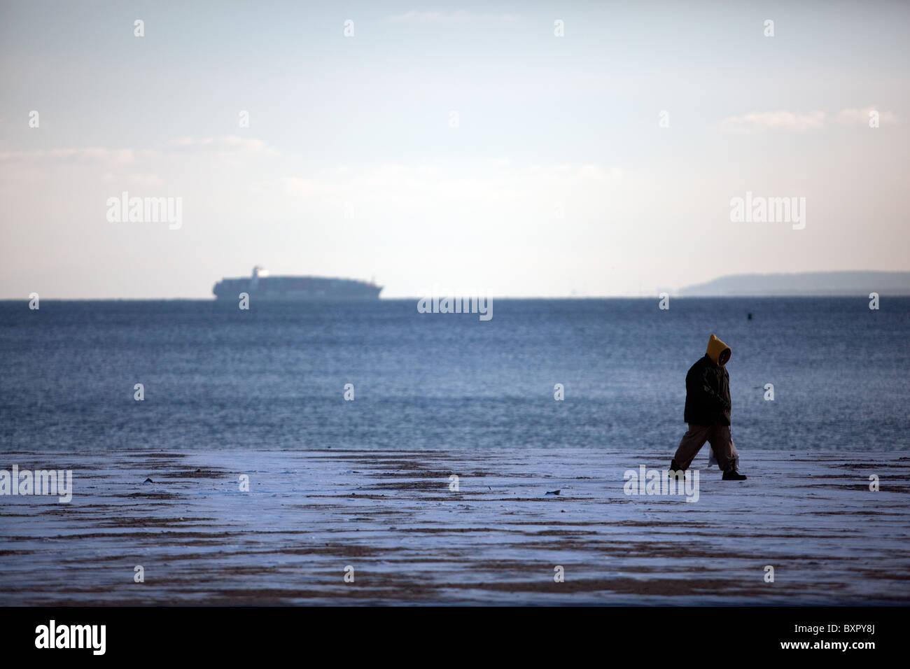Mann zu Fuß am Strand ein kalter Tag. kaltes Wetter Stockbild