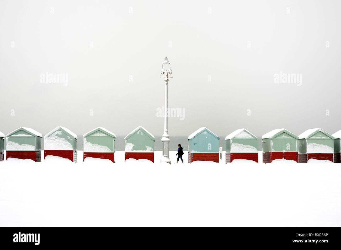 Ein Wanderer geht eine Reihe von Strandhütten mit Schnee bedeckt Stockbild