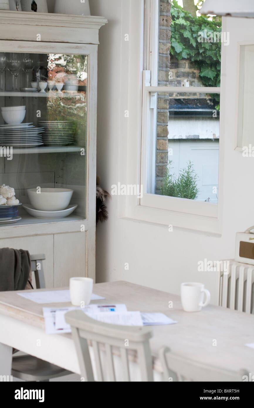 Küche mit weißen Esszimmer Einheiten und Tisch und Stühlen Stockbild