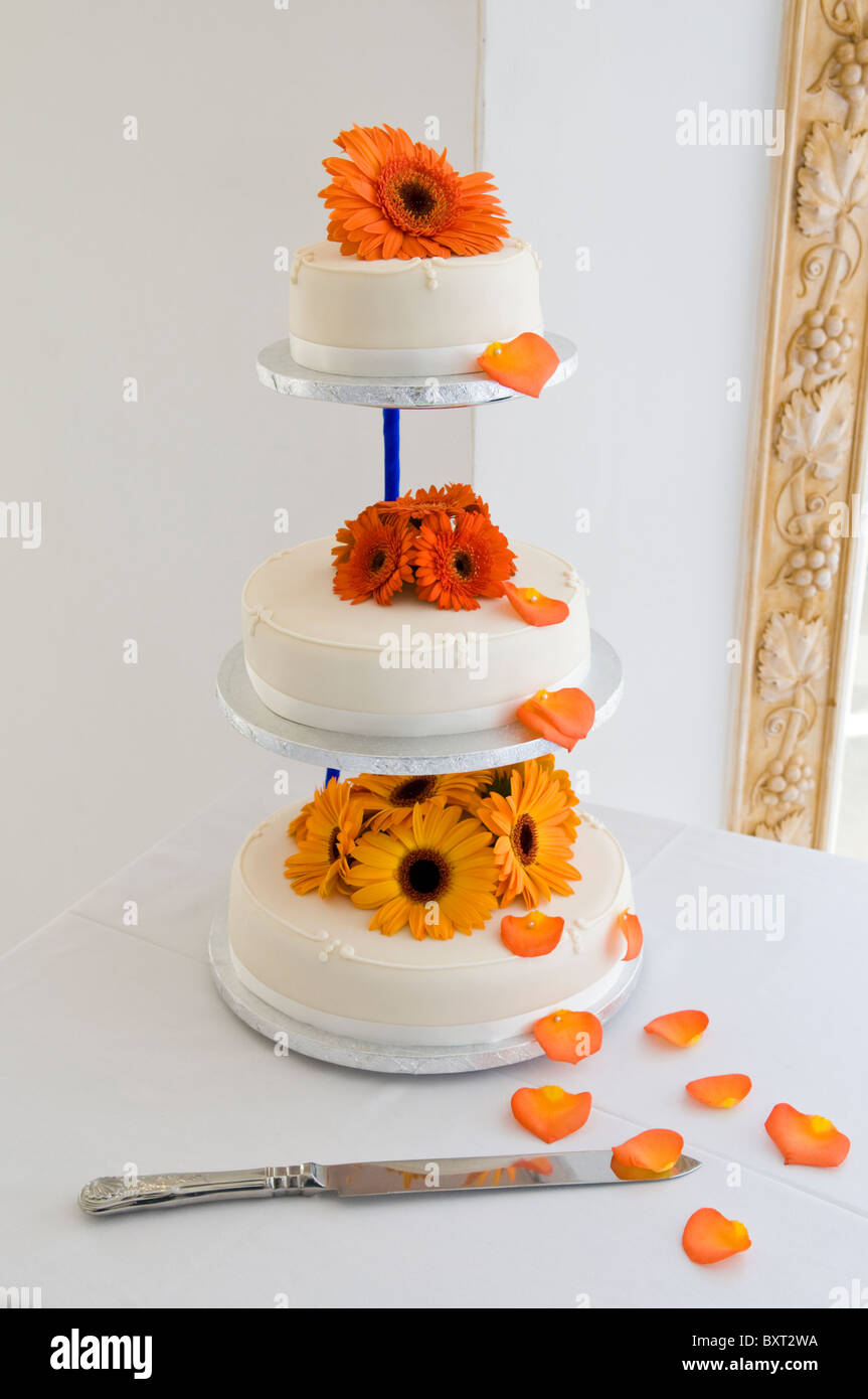 Orange Gerbera auf eine dreistufige Hochzeitstorte Stockbild