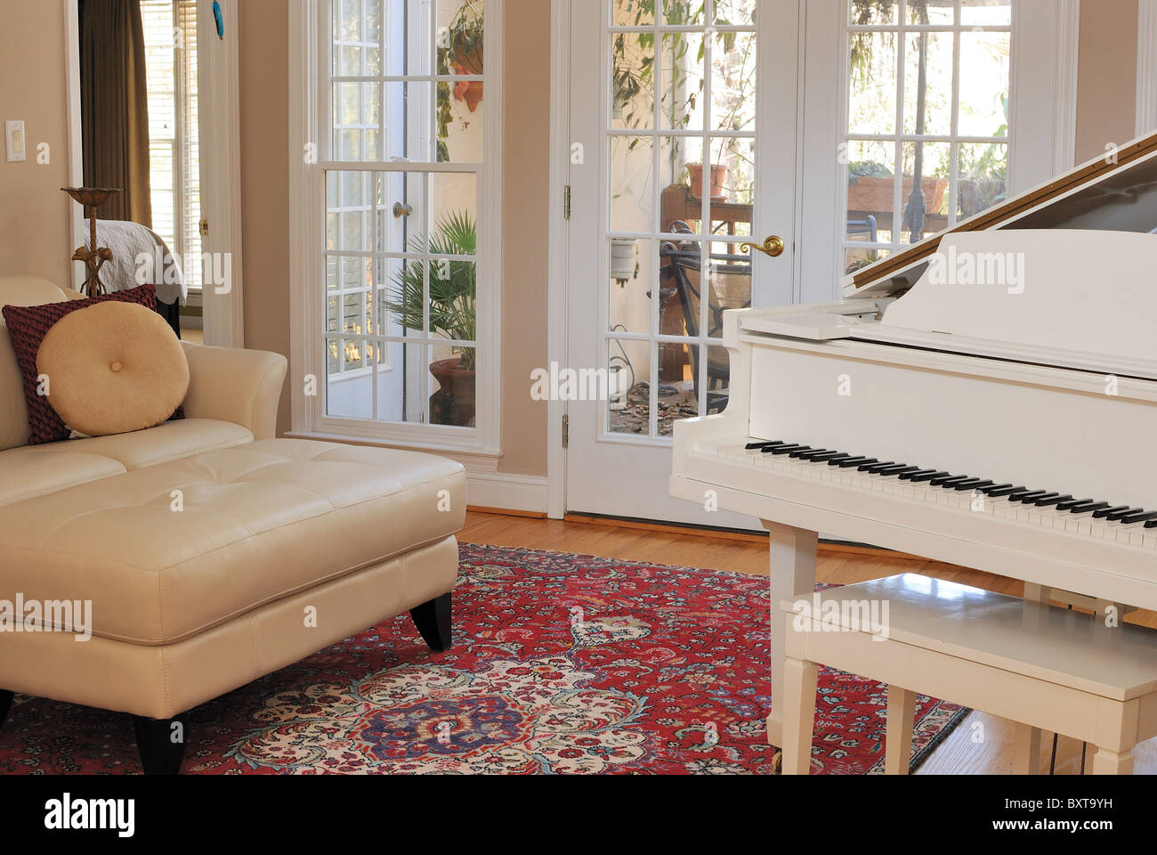 Zeitgenössische Wohnzimmer Einrichtung mit Sofa, Couch, Klavier und Fenster Blick auf die Terrasse Deck. Stockbild