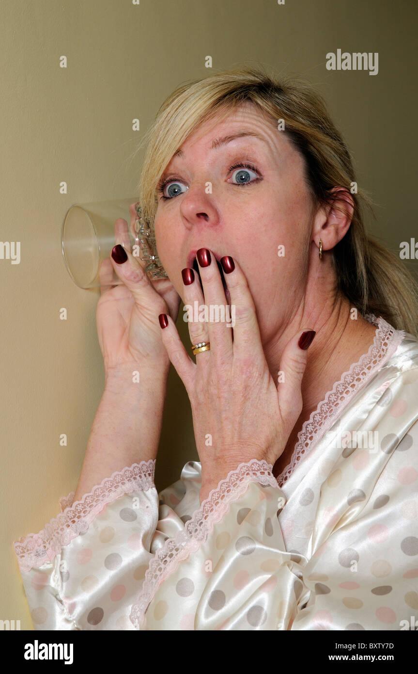 Frau Abhören nutzt ein Trinkglas zu Gesprächen auf der anderen Seite der Wand heimlich lauschen Stockbild
