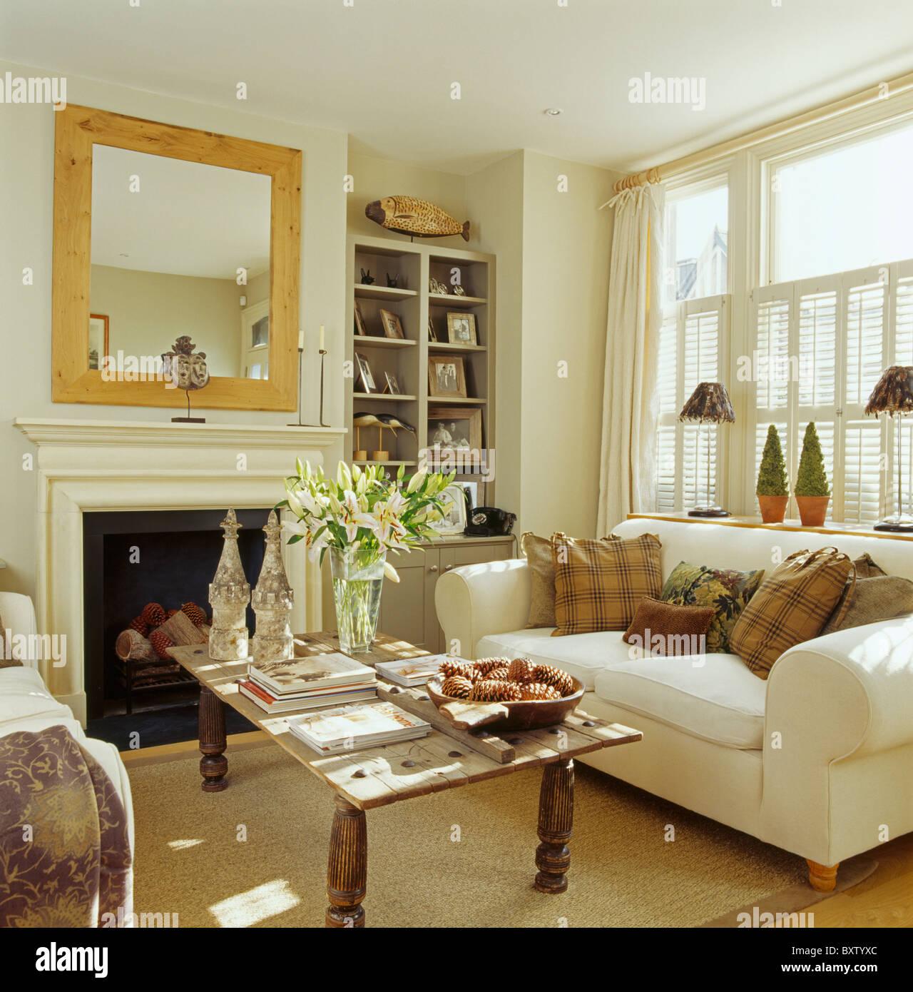 Rustikaler Holztisch Vor Sahne Sofa Mit Braunen Kissen In Creme Wohnzimmer  Mit Großem Spiegel über Dem Kamin