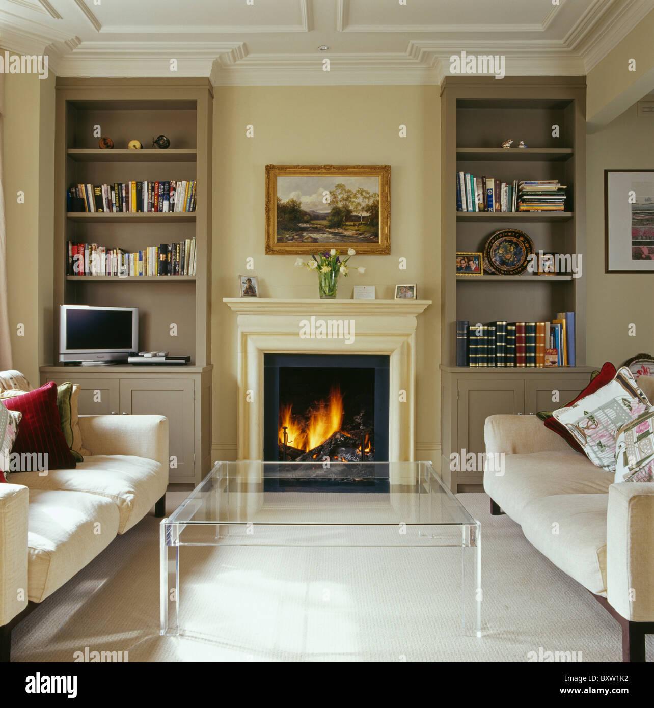 brennende feuer im kamin zwischen ausgestattete bcherregale im modernen wohnzimmer mit sofas in plexiglas tisch und sahne - Wohnzimmer Feuer