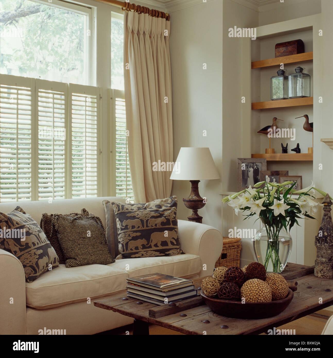 Cremefarbene Vorhänge Und Plantage Fensterläden Fenster Oben Sahne Sofa Mit  Gemusterten Kissen In Creme Wohnzimmer Mit Rustikalen Tisch