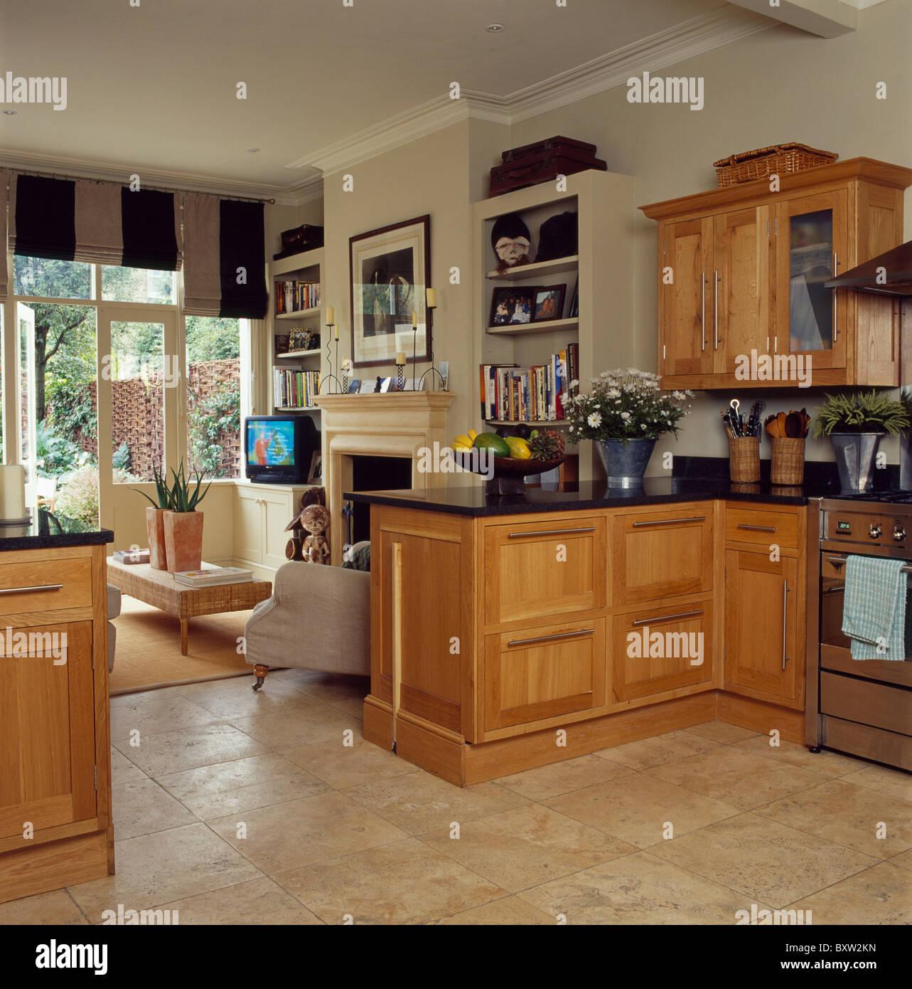 Kalkstein Bodenbelag und blasse Holz Einheiten in die offene Küche ...