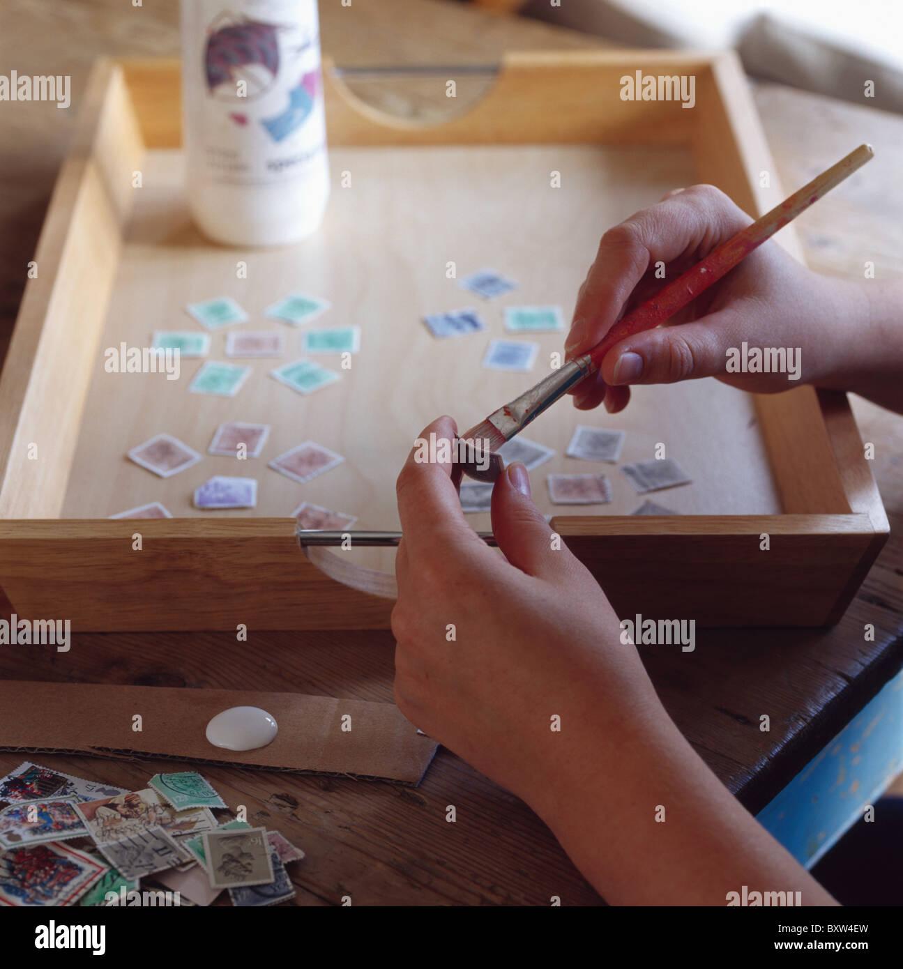 nahaufnahme der hände mit pinsel, alte briefmarken auf tablett aus
