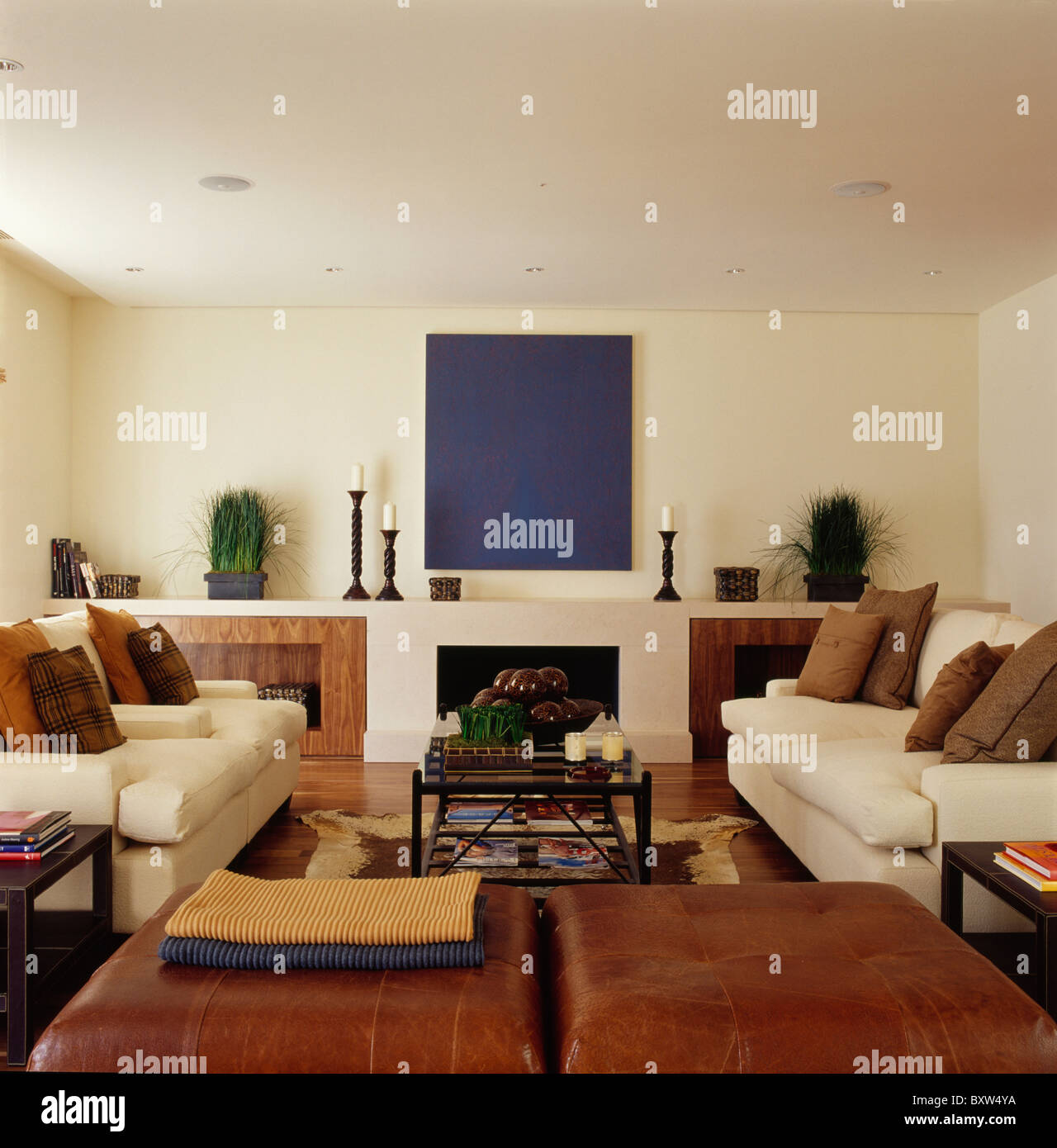 Abstrakte Gemälde An Der Wand über Dem Kamin Im Modernen Creme Wohnzimmer  Mit Braunem Leder Hocker Und Cremefarbenen Sofas