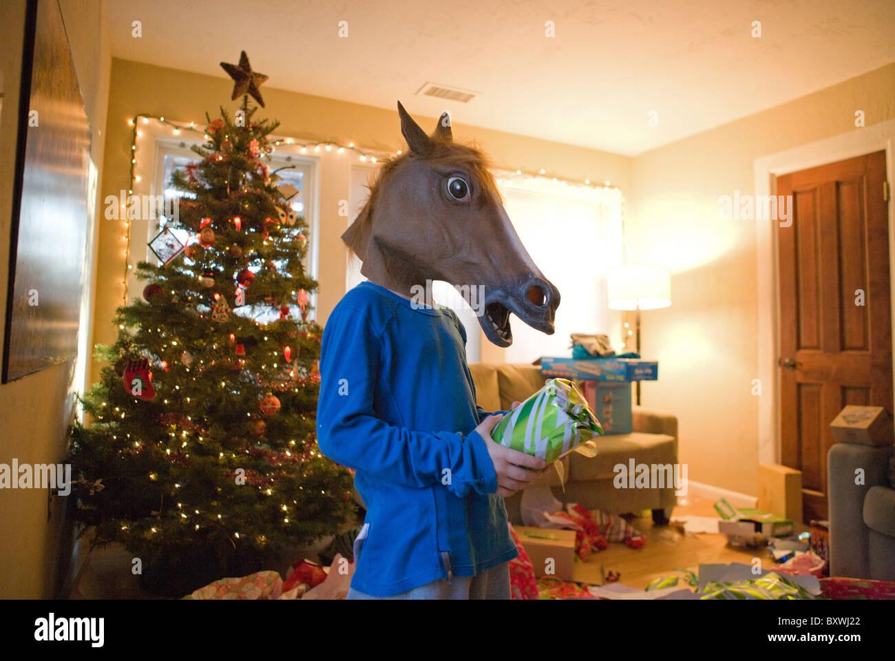 Ein Kind trägt eine Kopfmaske Pferd beim Öffnen in ein ...