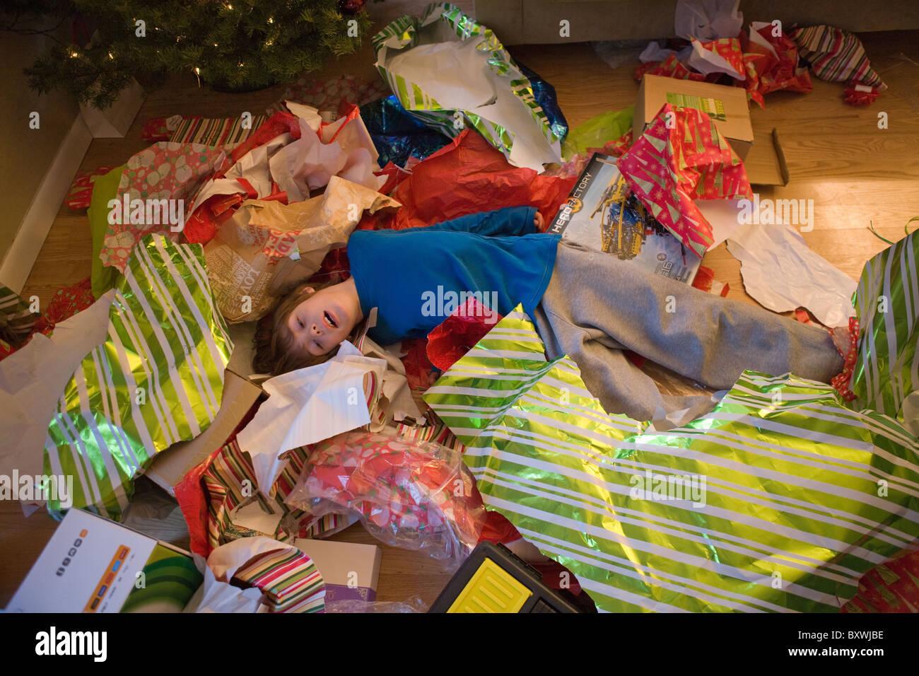Acht Jahre altes Kind auf dem Boden, müde nach dem Öffnen zu viele ...