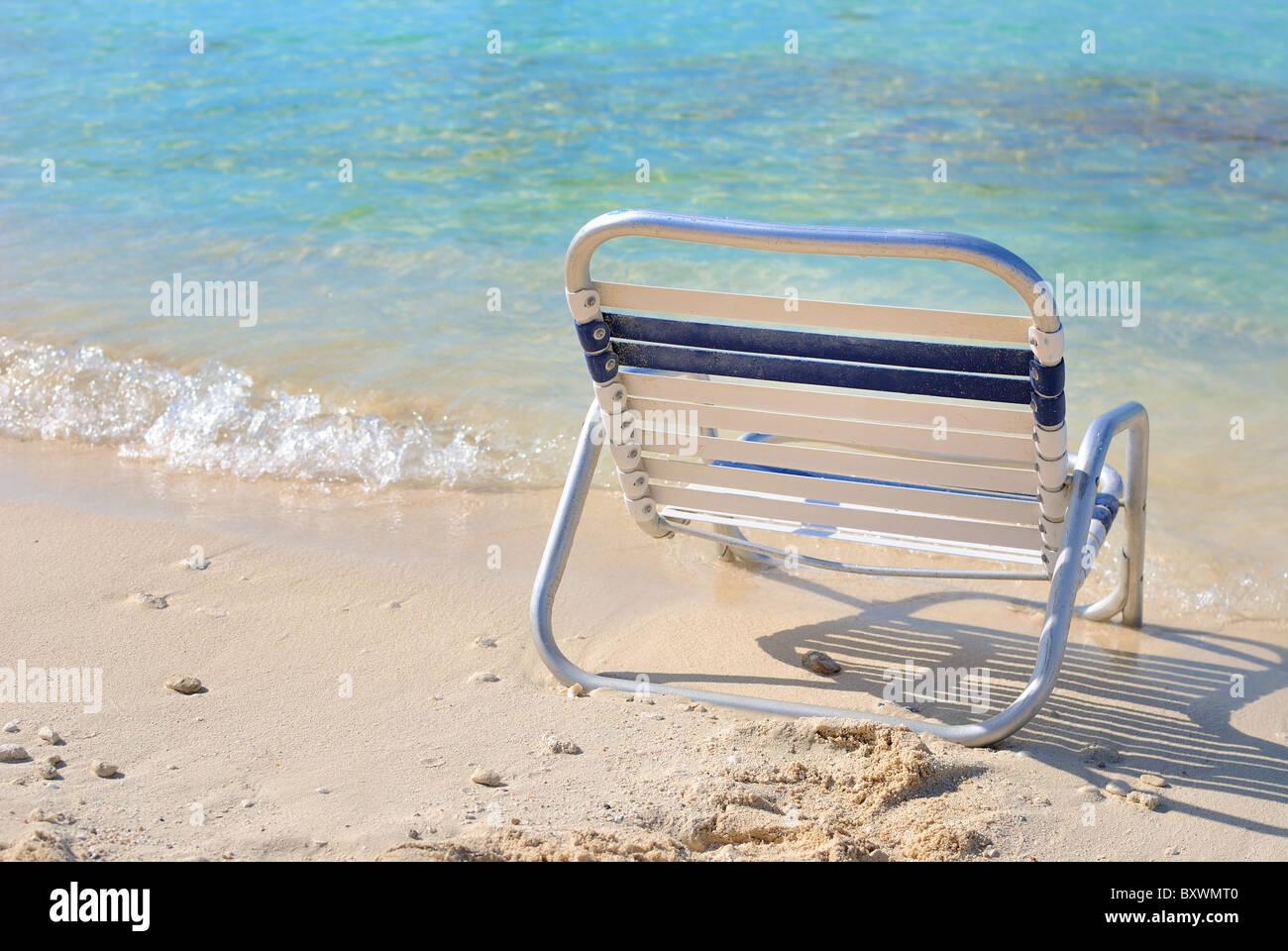 Entspannenden Liegestuhl in der Nähe von den Wellen des Ozeans Stockbild